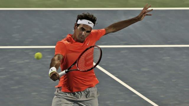 Roger Federer sin il plaz da tennis cun t-shirt oransch e rachet da tennis enta maun.