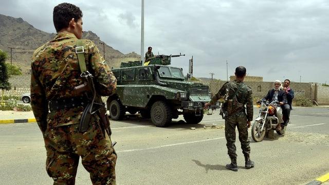 Soldaten stehen auf der Strasse, um zwei Männer auf einem Motorrad zu kontrollieren.