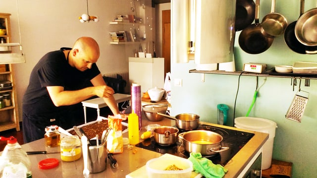 Ein Mann steht in einer Küche und würzt ein Essen.