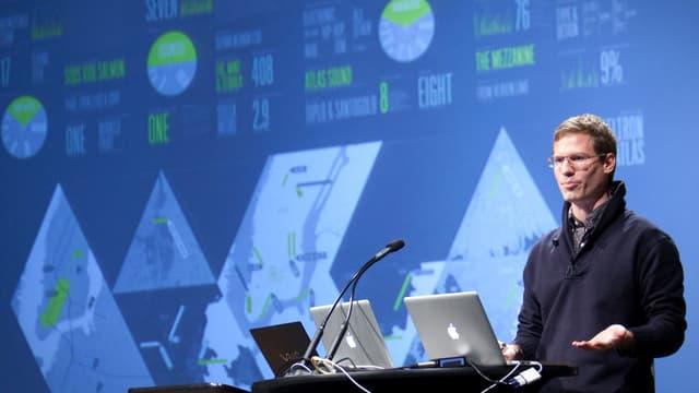 Nicholas Felton bei einer Präsentation vor lauter Grafiken und Diagrammen.