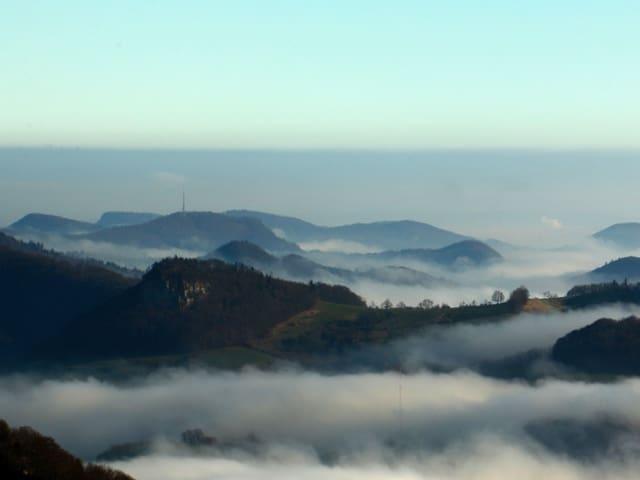Hüglige Landschaft mit Nebelschwaden in den Tälern.