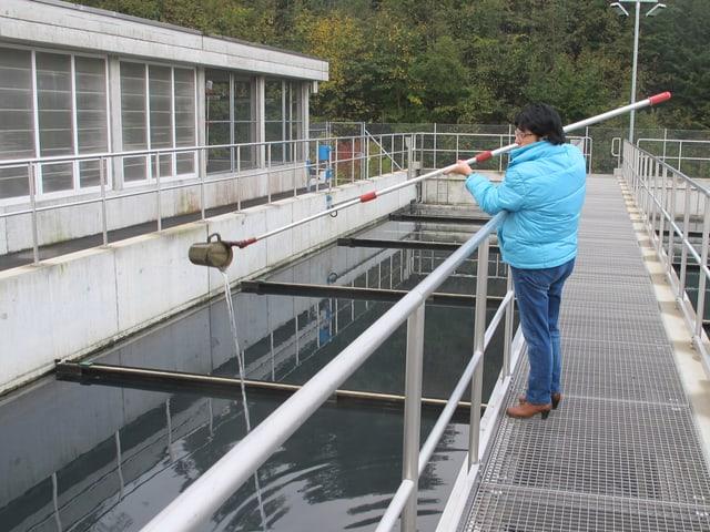 Regula Ammann nimmt eine Wasserprobe