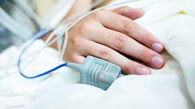 Eine Hand auf dem Spitalbett. Sie ist verkabelt.
