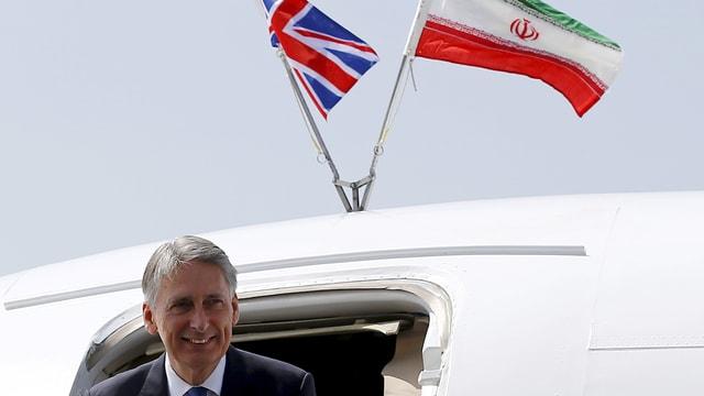 Hammond steigt aus einem Flugzeug, Flaggen von GB und Iran auf dem Dach.