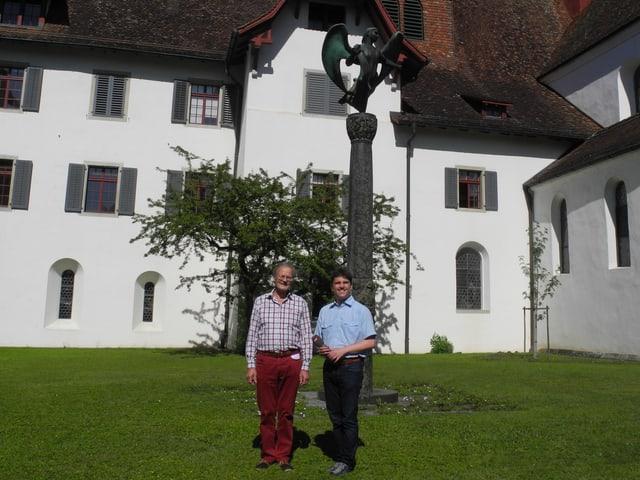 Zwei Männer stehen vor einer Kirche.