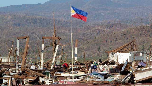 Eine Fahne inmitten eines Trümmerbergs.