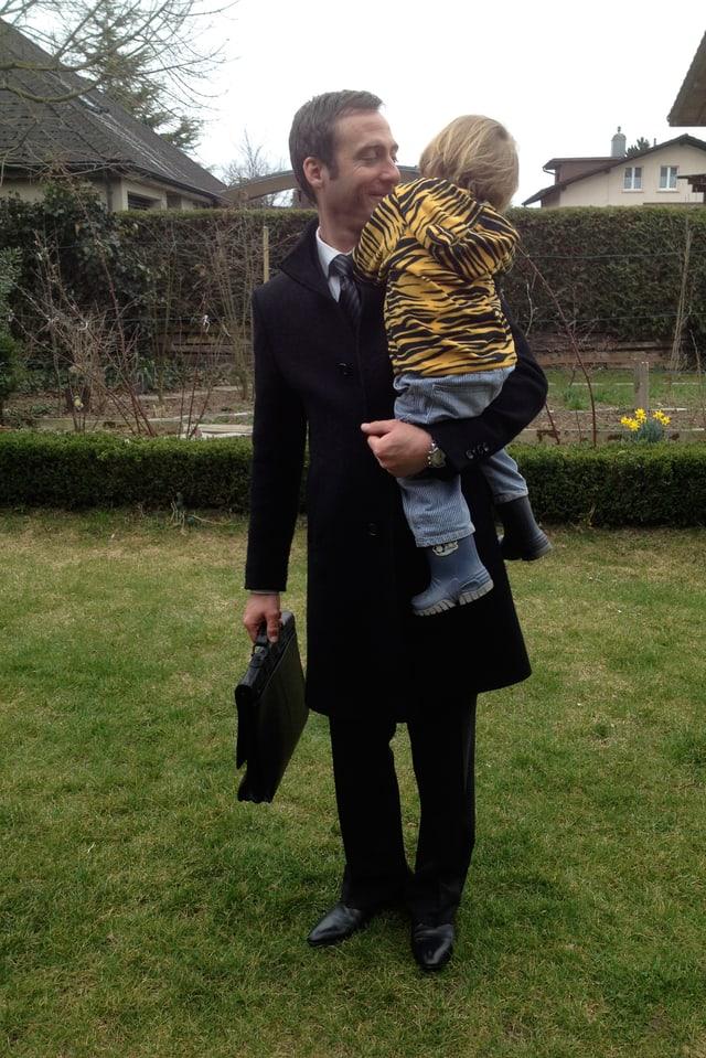 Elias Bartlome haät seinen Sohn Anatol auf seinem Arm. Sie stehen im Garten.