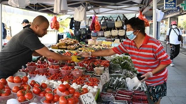 Ein Kunde mit Hygienemaske kauft Gemüse an einem Markt in London.