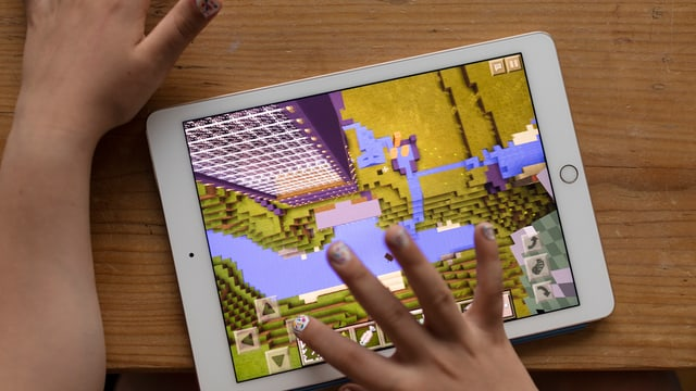 Ina mattetta dat in gieu sin in iPad - ins vesa mo l'iPad ed ils mauns pitschens cun unglas coluradas.