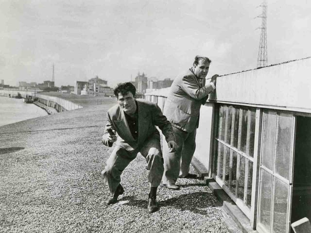 Schwarzweissbild: Zwei Männer, einer mit Pistole, ducken sich hinter einer Mauer.