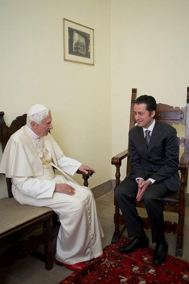 Papst sitzt neben Kammerdiener.