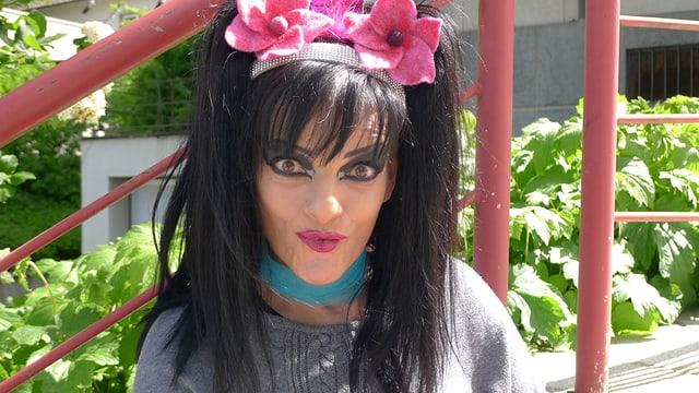 Nina Hagen, grell geschminkt, mit Haarband, an dem rosa Blumen befestigt sind. Sie spitzt die Lippen.