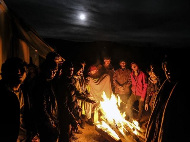 Männer sammeln sich um ein Feuer