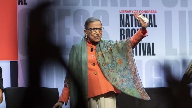Frau auf Bühne winkt ihren Fans.