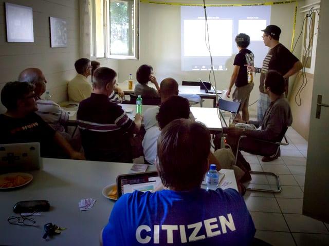 Ein dunkler Keller, 30 Leute sitzen vor einer Leinwand und vefolgen eine Präsentation