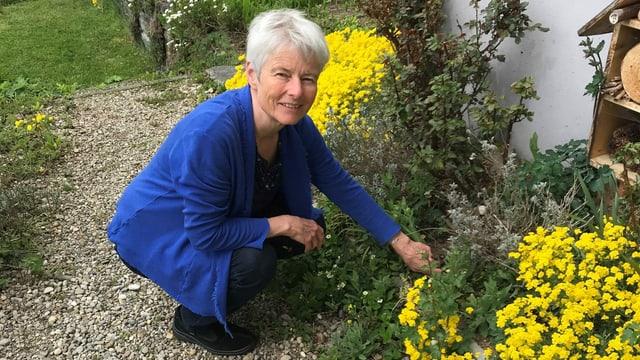Sandra Lutz kniet vor einem gelben Strauch in ihrem Garten.