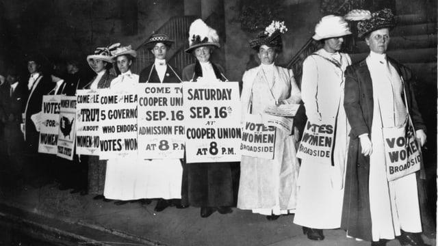 Frauen mit Hüten und weisser Kleidung mit Transparenten um den Hals