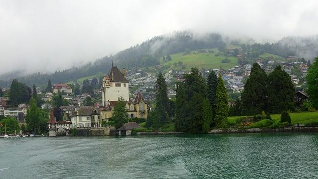 Schloss Oberhofen am grauen Thunersee, dahinter die Hügelzüge wolkenverhangen.