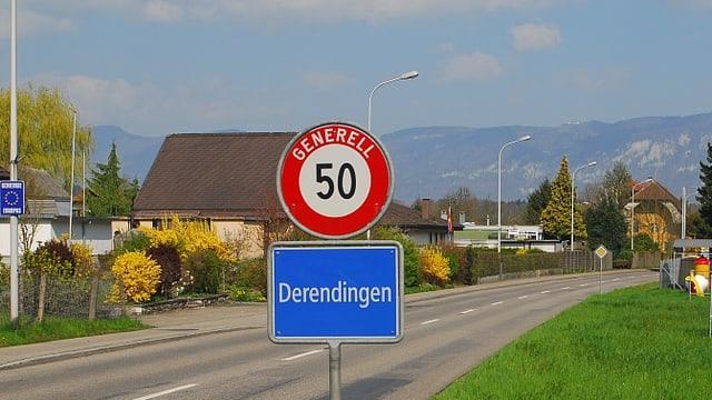 Ortstafel der Gemeinde Derendingen vor mehreren Häusern.