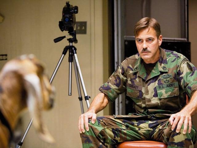 Ein Mann in Militäruniform sitzt auf einem Stuhl und starrt eine Zeige an.