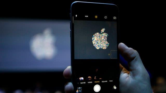 Hand hält iPhone in die Höhe und drückt auf Startknopf.