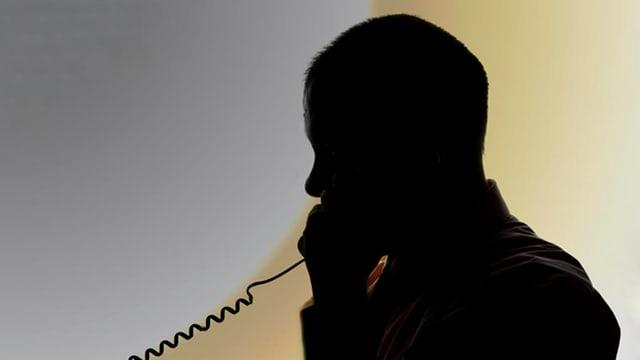 Silhouette eines Mannes, der telefoniert.