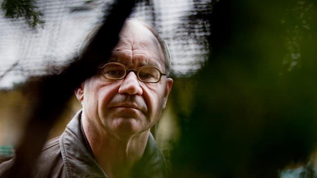 Portrait Rudolf Elmer, im Vordergrund unscharfes Gewächs.
