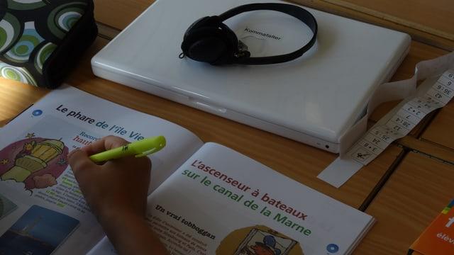 Ein Schüler schreibt in ein Heft. Vor ihm liegt ein Laptop.