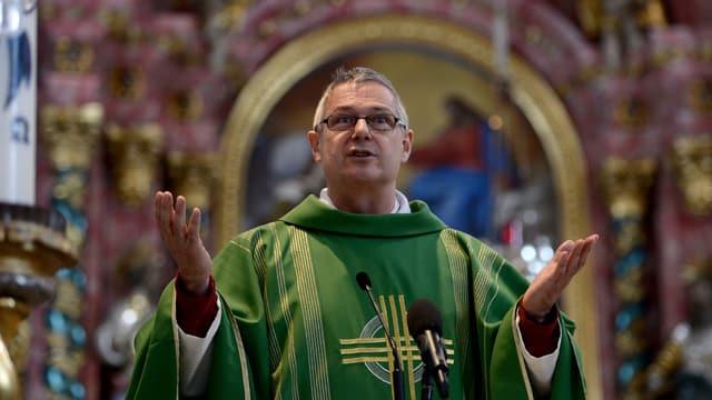 Pfarrer mit grüner Soutane in der Kirche