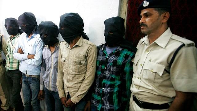 Fünf verhaftete Männer mit schwarzen Tüchern mit Augenlöchern um den Kopf und ein Polizist.