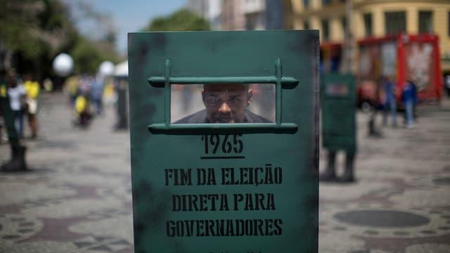 Ein Mann steht hinter einem Schutzschild, auf dem das Jahr 1965 und das Ende der freien Wahlen beklagt wird.