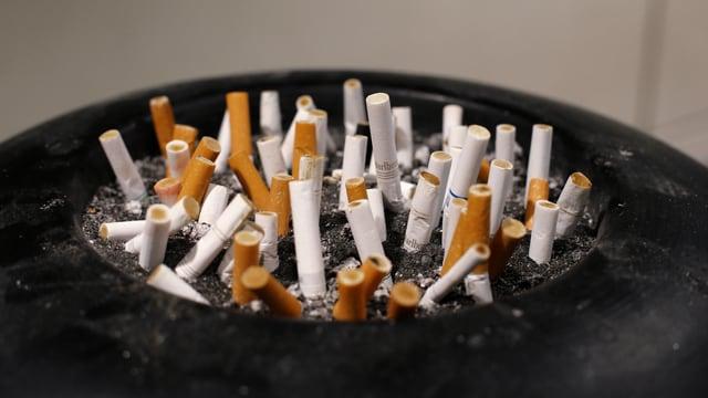 Ein Aschenbecher mit vielen Zigarettenstummeln.