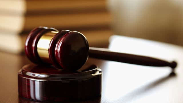 Bild eines Gerichtssaals mit einem Richterhammer, der auf dem Tisch des Richters liegt (Symbolbild).