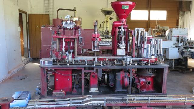 Eine weinrote, alte Maschine zum Weinabfüllen steht in einer Garage