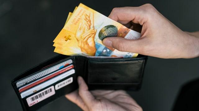 Eine Hand zieht Geld aus einem Portemonnaie.