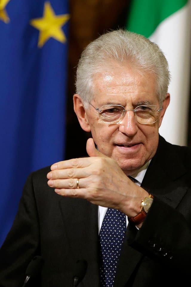 Mario Monti gestikuliert vor europäischen Länder-Flaggen.