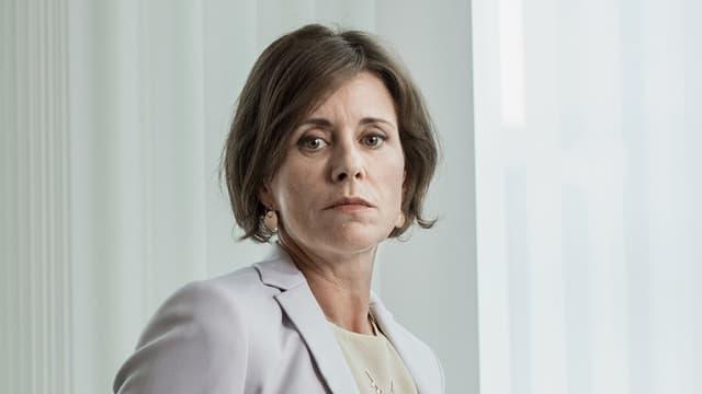 Eine Frau in hellem Blazer vor einem weissen Vorhang.