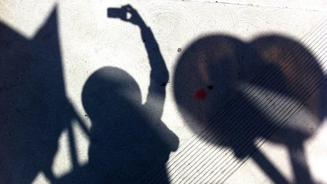 Schatten einer Person, die ein Selfie macht.