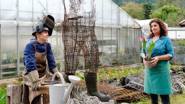 In einem Garten, vor einem Gewächshaus: Eine ältere Frau hält einen Topf mit einer Orchidee in der Hand und schaut eine jüngere Frau an. Diese sitzt neben einer halbfertigen Skulptur einer Person aus Draht.