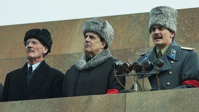 Drei kommunistische Männer am Redepult