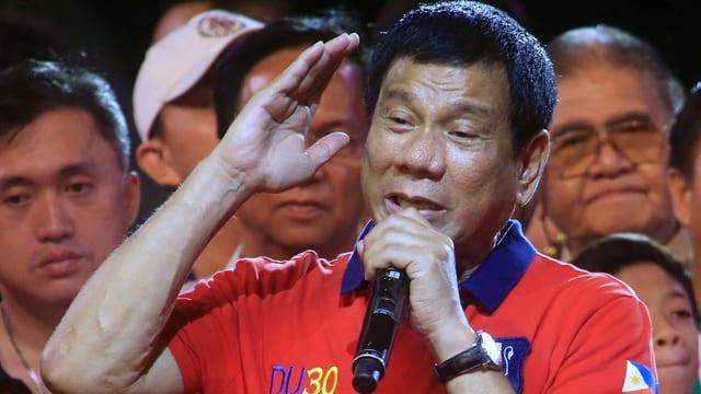 Rodrigo Duterte in einem roten Polo-Shirt und mit einem Mikrofon in der linken Hand.