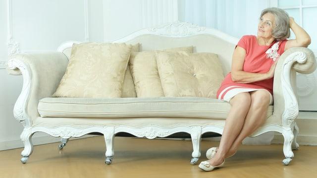Eine ältere Frau sitzt alleine auf einem Sofa.