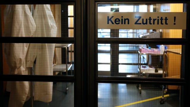 Blick auf eine geschlossene Schiebetür mit dem Schild «Kein Zutritt!», dahinter Medizinalausrüstung.