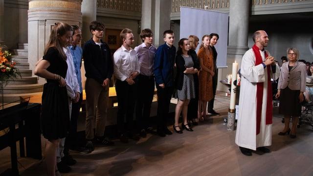 Pfarrer vor Konfirmanden stehend