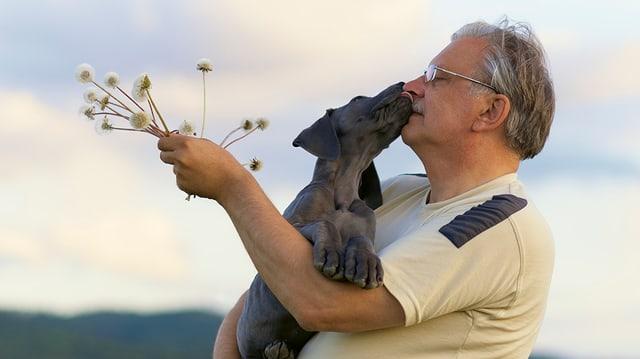 Ein Hund schleckt einem älteren Herrn, der Blumen in der Hand hält, übers Gesicht.
