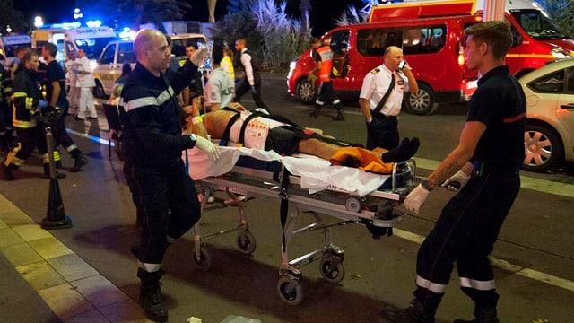 Rettungskräfte transportieren eine verletzte Person auf einer Bahre.