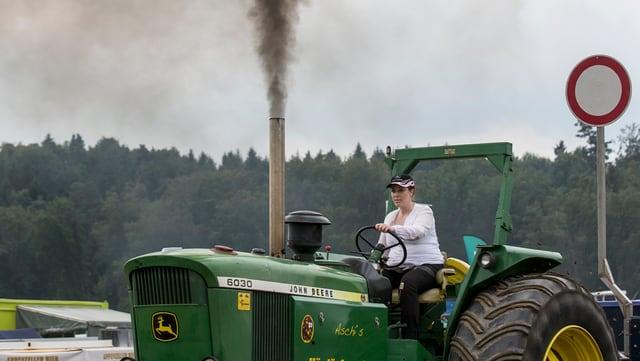 Grüner Traktor der Marke John Deere, der zu viel Abgase ausstösst.