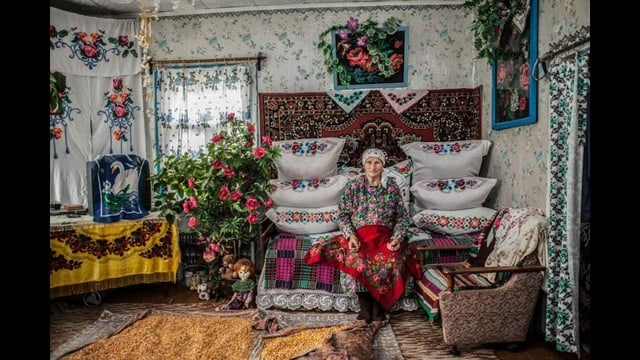 Eine ältere Frau sitzt in einem übbig mit Blumen und blumenmustern dekorierten Raum. Sie trägt ein buntes, traditionelles Kleid.