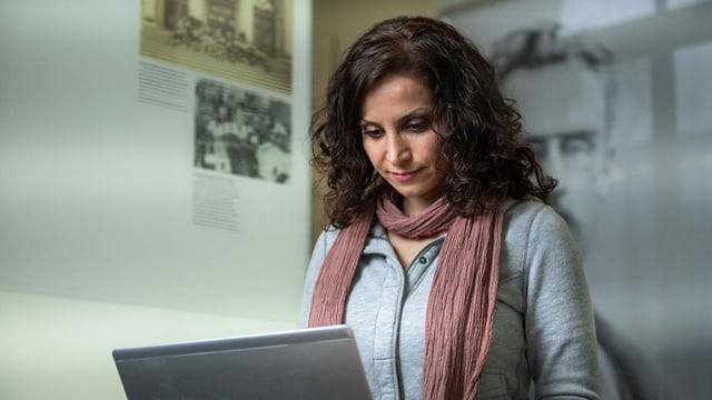 Eine junge Frau blickt vor einer Plakatwand in ihr Laptop.