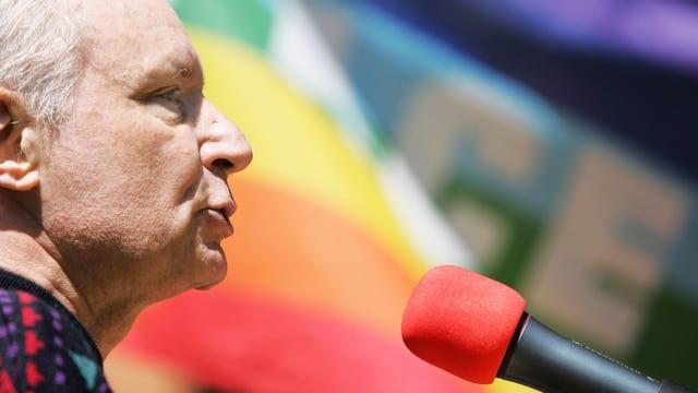Eugen Drewermann vor einer Peace-Fahne.